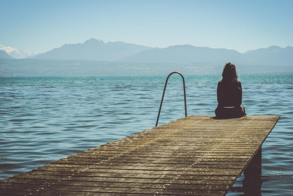 lonely woman sitting at end of a wooden dock