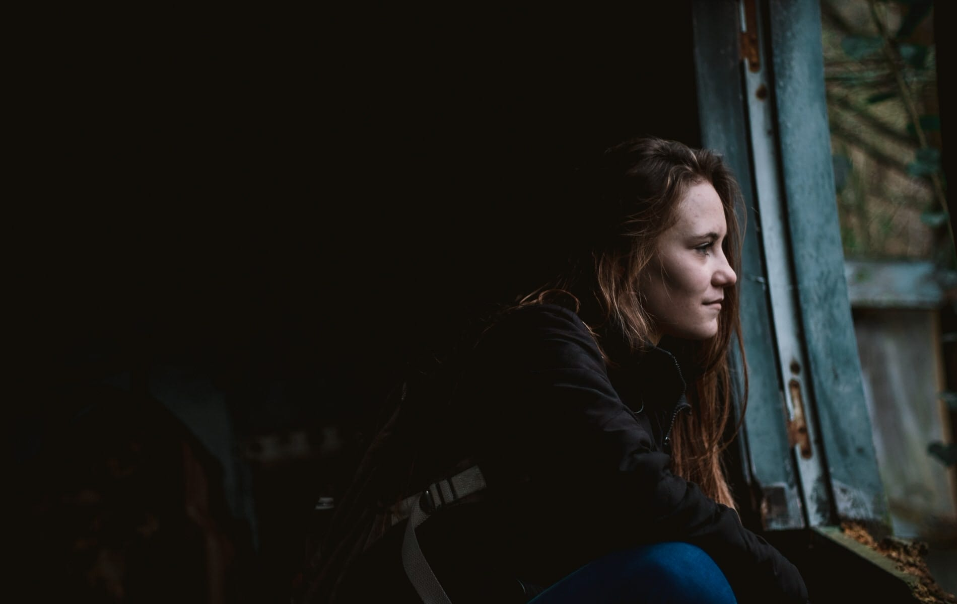 sad young woman looking out a window